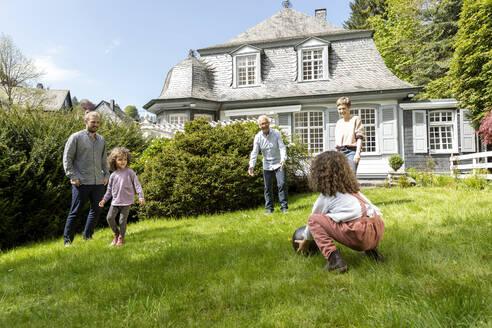 Happy extended family playing football in garden - MJFKF00133