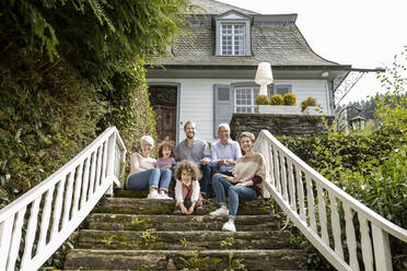Happy extended family sitting on stairs in garden of their home - MJFKF00136