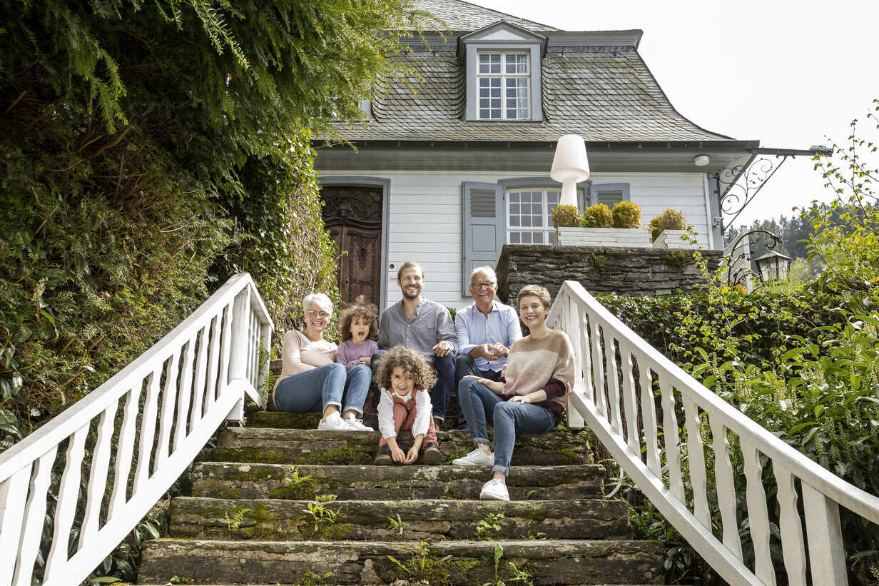 Happy extended family sitting on stairs in garden of their home - MJFKF00136 - MiJo/Westend61