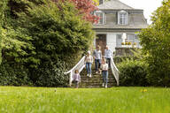 Extended family walking on stairs in garden of their home - MJFKF00139
