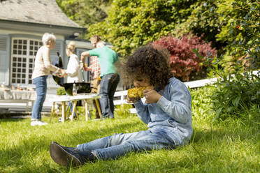 Boy eating a corn cob on a family barbecue in garden - MJFKF00145