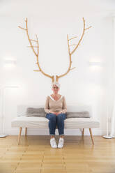 Mature woman sitting under wooden antlers at home - MJFKF00151