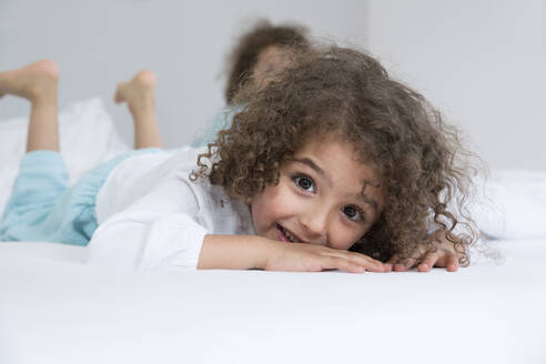 Portrait of happy boy with his brother in bed - MJFKF00157