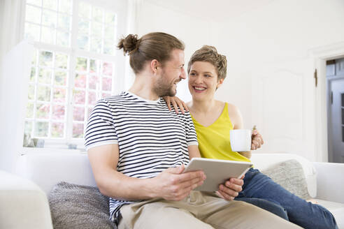 Happy young couple using tablet on couch at home - MJFKF00172