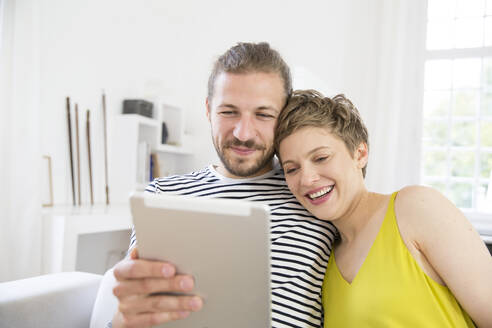 Young couple using tablet at home - MJFKF00175