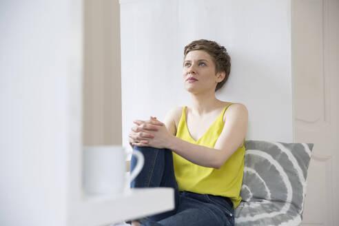Pensive woman sitting at home - MJFKF00181