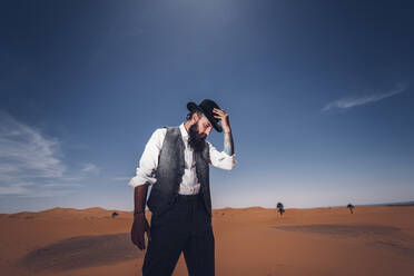 Man with a beard and hat in the dunes of the desert of Morocco - OCMF00712