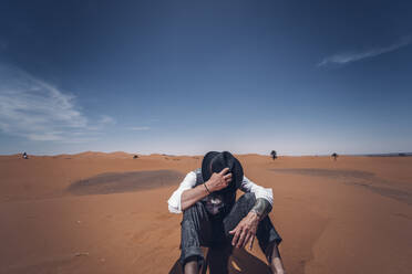 Man putting on his hat in the dunes of the desert of Morocco - OCMF00715
