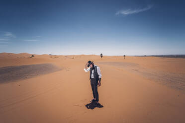 Man with a beard and hat in the dunes of the desert of Morocco - OCMF00718
