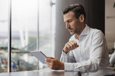 Businessman using tablet in a cafe - DIGF08410