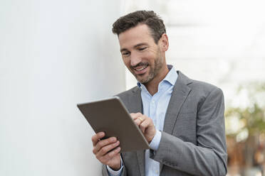 Smiling businessman using tablet in the city - DIGF08419