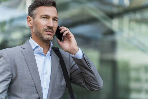 Businessman on cell phone in the city - DIGF08425