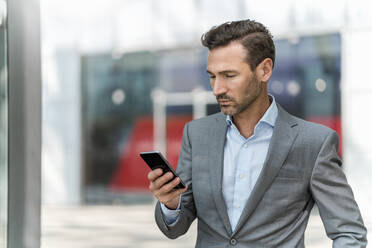 Businessman using cell phone in the city - DIGF08434