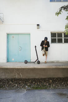 Man with Electric Scooter leaning against facade using smartphone - PSIF00314