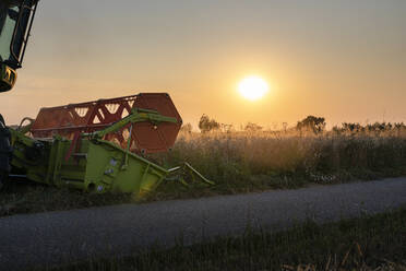 Organic farming, wheat field, harvest, combine harvester in the evening - SEBF00214