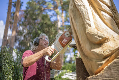 Wood carver carving sculpture, using chainsaw - BFRF02058