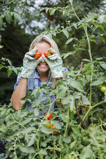 Blond smiling woman harvesting tomatoes, tomatoes on eyes - HMEF00523