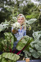 Blond smiling woman harvesting kohlrabi - HMEF00526