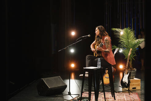 Female musician playing guitar and singing on stage - HEROF38594