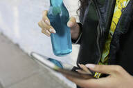 Close up woman with smart phone drinking soda - HEROF38804