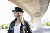 Confident, cool young woman under urban overpass - HEROF38822