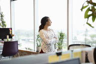 Thoughtful businesswoman looking out office window - HEROF38837