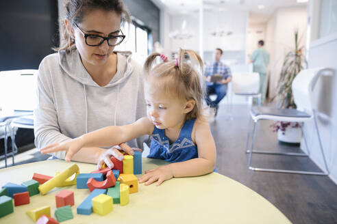 Mother and toddler daughter playing with building blocks in clinic waiting room - HEROF39038