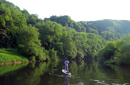 Paddle boarder deep in the Wye Valley Gorge, River Wye, Monmouthshire, Wales, United Kingdom, Europe - RHPLF09206