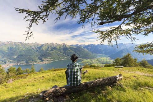 Man sitting on tree trunk looks towards Lake Como and Alto Lario, Monte Legnoncino, Lecco province, Lombardy, Italy, Europe - RHPLF09239
