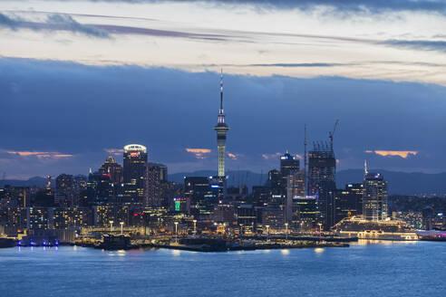 Illuminated modern buildings by sea against cloudy sky at dusk, Oceania, New Zealand - FOF10885