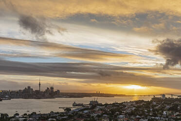 Aerial view of Auckland Harbour Bridge over sea against sky in city at sunset, New Zealand - FOF10888