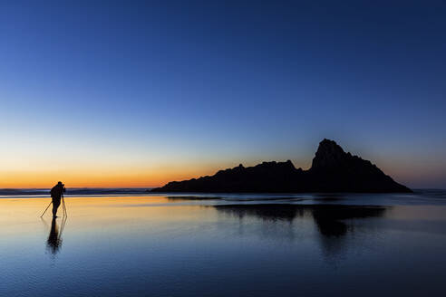 Tourist photographing while standing at Karekare beach against clear sky during sunset, New Zealand - FOF10909