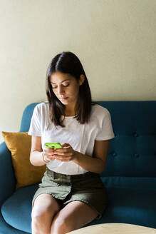 Young woman sitting on a couch using cell phone - GIOF07065
