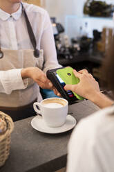 Close-up of customer paying cashless with smartphone in a cafe - GIOF07083