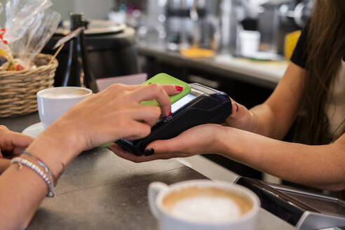 Close-up of customer paying cashless with smartphone in a cafe - GIOF07086