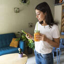 Young woman with a smoothie using cell phone in a cafe - GIOF07098