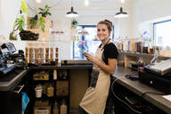 Portrait of smiling young woman with cell phone behind the counter in a cafe - GIOF07101