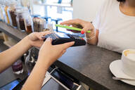 Close-up of customer paying cashless with smartphone in a cafe - GIOF07104