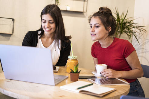 Two young women using laptop in a cafe - GIOF07119