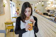 Young woman drinking a smoothie in a cafe - GIOF07125