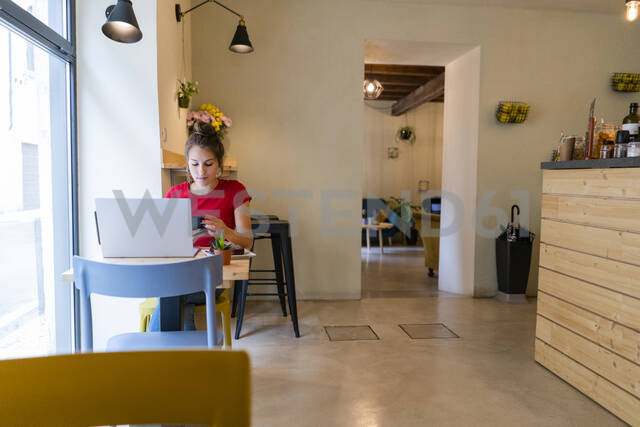 Young woman with cell phone and laptop in a cafe - GIOF07128 - Giorgio Fochesato/Westend61