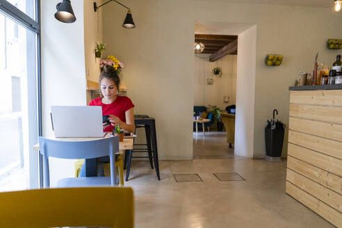 Young woman with cell phone and laptop in a cafe - GIOF07128