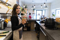 Portrait of smiling young woman behind the counter in a cafe - GIOF07134