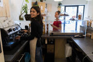 Portrait of smiling young woman preoaring a coffeer in a cafe - GIOF07137