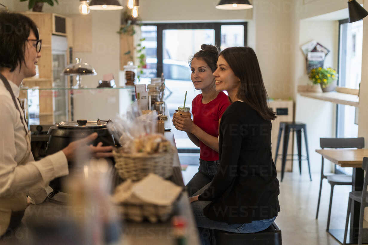 Two young female friends in a cafe talking with barista - GIOF07140 - Giorgio Fochesato/Westend61