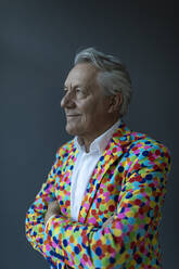 Senior businessman wearing colorful sports jacket looking away - GUSF02538