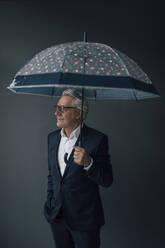 Senior businessman holding umbrella looking away - GUSF02541