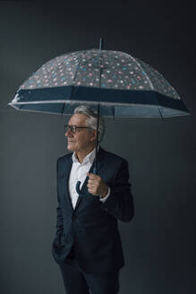 Senior businessman holding umbrella looking away - GUSF02541