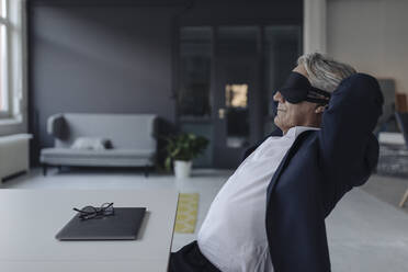 Senior businessman wearing eye mask at desk - GUSF02544