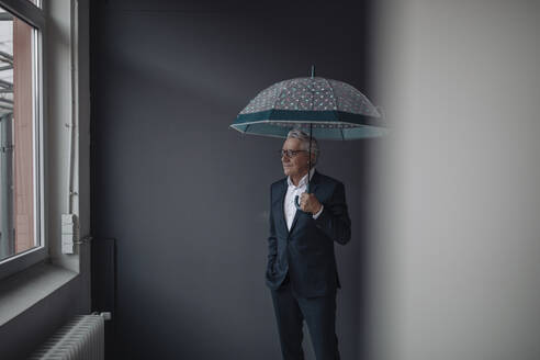 Senior businessman holding umbrella - GUSF02547